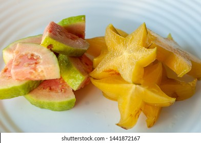 Carambola and organic guava on white plate, slices of carambola and red guava, carambola fruit salad.  Star fruit.
