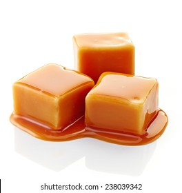 caramel candies and caramel sauce isolated on a white background
