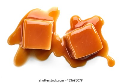 caramel candies and sauce isolated on white background, top view