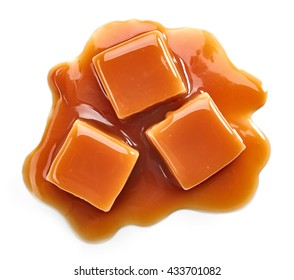 caramel candies and sweet sauce isolated on white background, top view