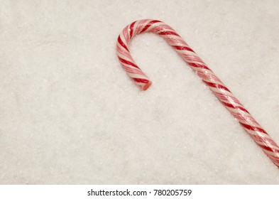 Caramel cane with white and red stripes with the taste of peppermint on fluffy snow