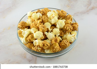 Caramel and cheddar popcorn on glass snack bowl on table