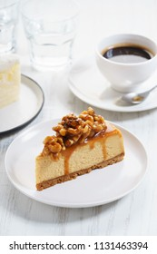 caramel cheese cake with coffee on white wooden table