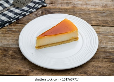 caramel cheesecake on white plate on wooden table