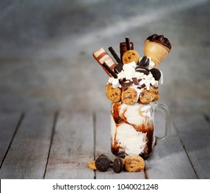 Caramel and chocolate indulgent exreme milkshakes with chocolate cake, oreo, marshmallow and sweets. Crazy freakshake food trend. Copy space, ice cream in a cube,
