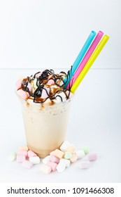 Caramel and chocolate indulgent extreme milkshakes with marshmallow, ice cream and whipped cream. Crazy freakshake food trend. on white bakground