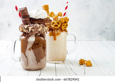 Caramel and chocolate indulgent extreme milkshakes with brezel waffles, popcorn, marshmallow, ice cream and whipped cream. Crazy freakshake food trend.