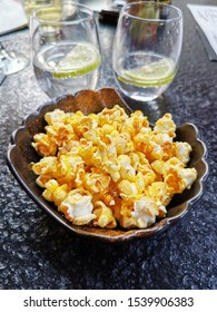 Caramel coated popcorn with water and lemon in the background
