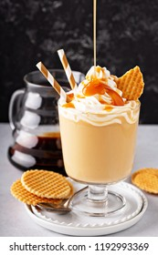 Caramel coffee latte in a dessert glass with whipped cream and syrup