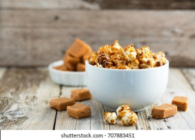 Caramel covered popcorn and caramel toffees. On wooden table. Natural light, selective focus.