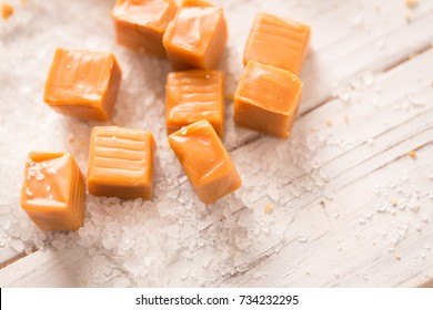 Caramel Cubes and Sea Salt Close Up on White Wood. an above close up macro shot of caramel cubes with sea salt all around on a white wood board