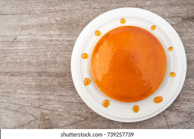 Caramel custard cake on white plate. Sweet and moist dessert.  Top view over wooden table. Decorate with caramel. With copy space.