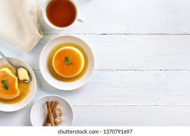 Caramel custard dessert and cup of tea on wooden background with copy space. Top view, flat lay
