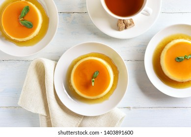Caramel custard pudding on light wooden background. Top view, flat lay