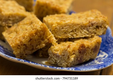Caramel flapjacks on a dish with wood background