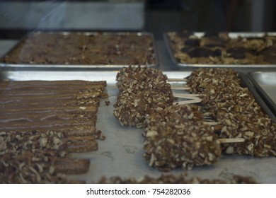 Caramel and nuts on pretzels and marshmallows on a metal tray in candy store window.