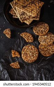 Caramel peanut brittle from sunflower seeds and sesame seeds and fitness cookies with flax seeds on dark black concrete background.