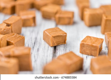 Caramel pieces as high detailed close-up shot on a vintage wooden table (selective focus)