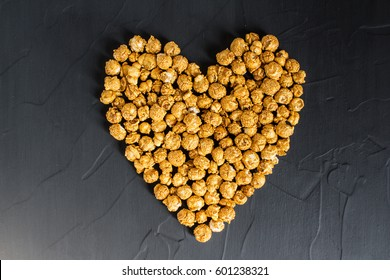 Caramel popcorn in heart shape. Love popcorn concept. Horizontal photo. Sweet food