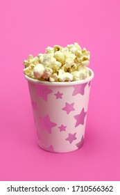 caramel popcorn in a paper Cup on a pink background