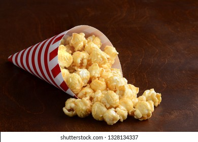 caramel popcorn in a red and white paper cone