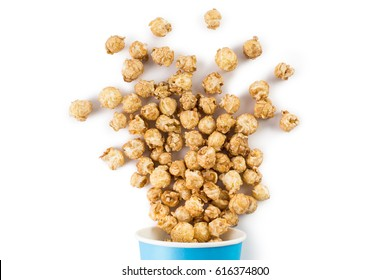 Caramel popcorn scattered out of a blue bucket, isolated on white background