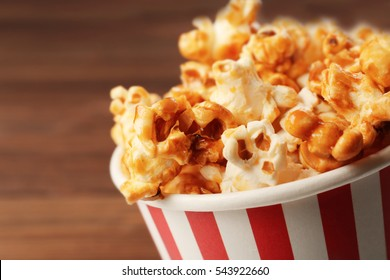 Caramel popcorn in striped box on wooden background
