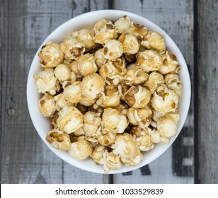 Caramel popcorn in white bowl on wooden background, top view.