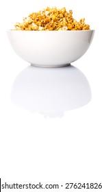 Caramel popcorn in white bowl over white background