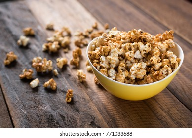 caramel popcorn in a yellow bowl on a wooden table background. popcorn in a bowl and scattered on table