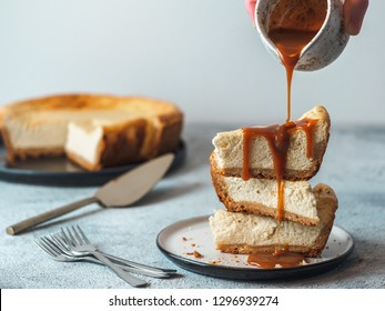 Caramel pouring on stack of three cheesekace pieces. Cheesecake with caramel on gray cement background. Copy space for text.