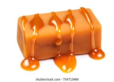 Caramel sauce flowing on caramel candies, isolated on white background. Golden Butterscotch toffee caramel liquid