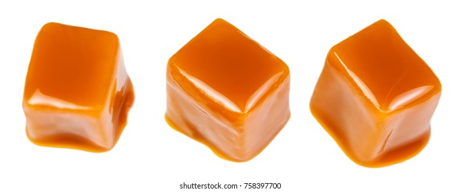 Caramel sauce flowing on caramel candies, isolated on white background. Golden Butterscotch toffee candy
