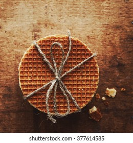 Caramel waffles tied up with jute bow with copy space on brown background, table top view
