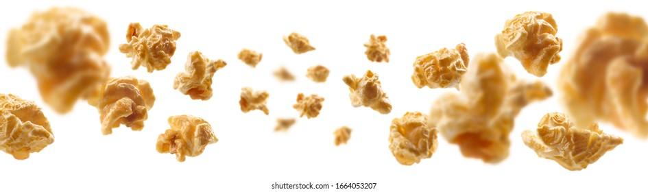 Caramel-flavored popcorn levitates on a white background