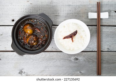 Caramelized balut - boiled developing duck embryo in a clay pot and a bowl of rice