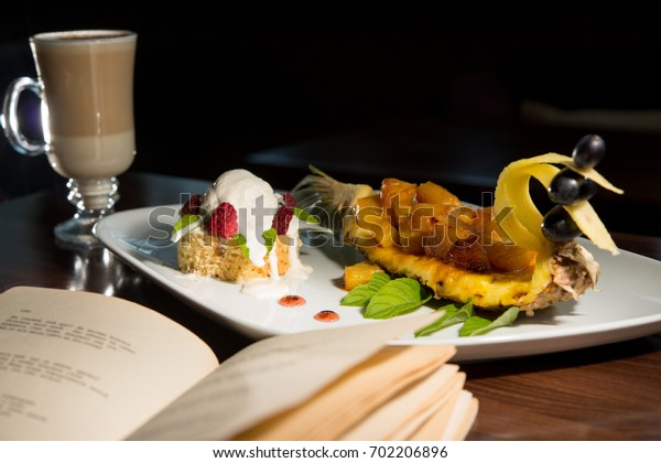 Caramelized pineapple in the form of bird fever, a glass with latte, ice cream with raspberries and an open book