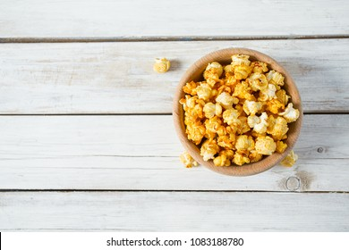 caramelized popcorn on blue wooden surface