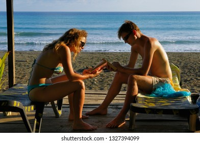 Carate, Costa Rica - March 16, 2008: Young couple on vacation at Carate Costa Rica reading books on the beach
