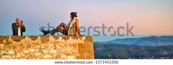 Caravaca, Spain, January 7, 2019: Tourist couple taking photo on the precipice of Caravaca castle in Spain. Dangerous pictures. Risky photos in cliffs. Death risk, tourists pictures, photos, selfies.