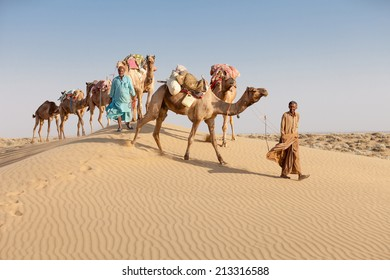Caravan with bedouins and camels on sand dunes in desert at sunset. Thar desert or Great Indian desert.