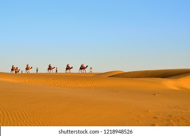 A Caravan of Camels carrying tourists in Sam Sand Dunes, Thar Desert, Jaisalmer, India. Located in the midst of the Thar Desert, these sand dunes are amongst the most famous ones in Rajasthan.
