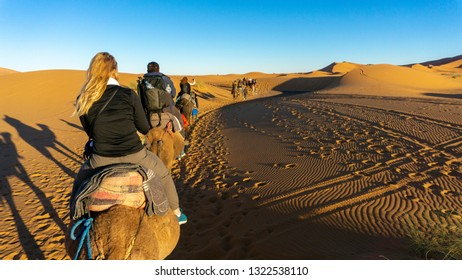 Caravan camels with tourists going into the Sahara Desert, near Merzouga, Morocco - small town known as a gateway to Erg Chebbi - huge expanse of sand dunes north of town. Day trip adventure.