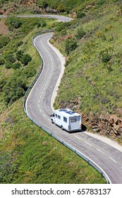 Caravan camper motorhome or camping home van car on the winding rural highway road among green landscape during recreational summer holiday journey in the France, Europe