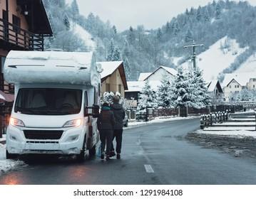 caravan camper van vehicle for van life  winter holidays on camper van journey camping in mountains near the forest in the winter adventure season, snowing on the campervan