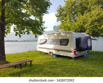 caravan car on the camping green grass and tress beside lake water