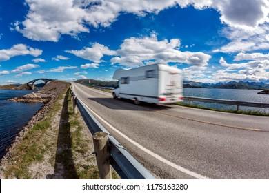 "Caravan car RV travels on the highway. Caravan Car in motion blur. Norway. Atlantic Ocean Road or the Atlantic Road Atlanterhavsveien been awarded the title as ""Norwegian Construction of the Century""."