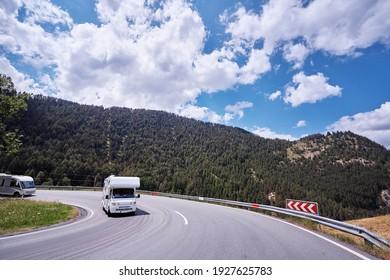 Caravan car travels on the highway in Alp Mountains. Traveling concept. Camper vans.