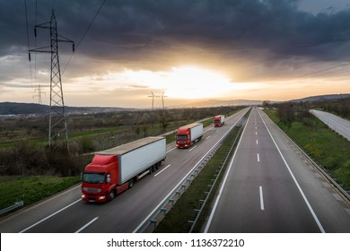 Caravan or convoy of red trucks in line on a country highway