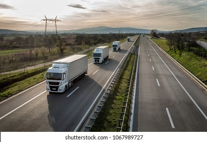 Caravan or convoy of trucks in line on a country highway - Shutterstock ID 1067989727